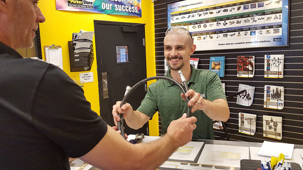 Parker Store representative, handing customer a completed hose assembly. Image